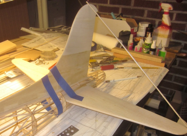 "B-17-13-36     With plenty of Deluxe Materials Aliphatic Resin brushed in place, I lined up the fin installation and squared it off just as I did with the horizontal tail. The blue tape is doing the job of holding everything in place; the light diagonal ""brace"" is just to ensure that the alignment is maintained while the glue dries."