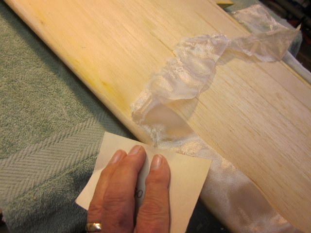 PT-19-42   When that happens it looks like this.  A piece of 100-grit paper in my hand easily cuts away the unattached/unsaturated  (extra) glass cloth right back to where it's properly bonded to the balsa surface.