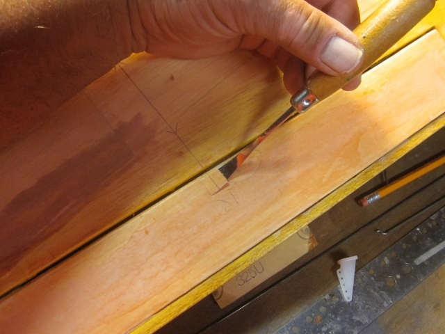 "PT-19-45   A little diversion…I need the aileron horn in place to line up the pushrod exit hole in the wing skin. I have marked a line directly back from the servo output to locate both the pushrod exit opening and the control horn itself. Here I'm using a small chisel to open a hole in the 3/32"" balsa sheet aileron skin for the rectangular base of the nylon control horn to seat into. (I prepared for this earlier by building in a wide basswood block INSIDE the aileron to provide a strong mounting base.) The next step is to attach the horn…"