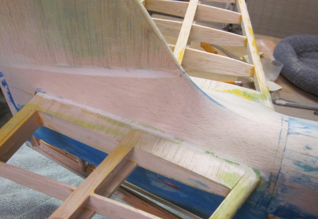 "PT-19-53   Here's a good look at the horizontal stabilizer all stripped clean of film covering. (We'll forget about the elevator for now.) To get that right…to represent a plywood-skinned surface…I could cut it all off and start over, insert/recess the outer edges of every rib as well as the outer faces of the top and bottom spars and ""inlay"" a new sheet covering the way I did on the wing, or smooth off the existing surface and skin over it. If I did THAT with 1/64"" plywood the extra thickness of the completed structure would be inconsequential, the ""scale"" appearance of the model would be acceptable, and that's what I did."